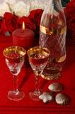 Celebration. Liquor glasses, bottle, Belgian chocolate, candle and roses Stock Photo