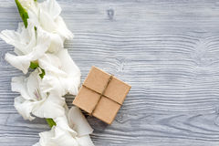 Celebration accessories. Box in kraft paper near flower gladiolus on light wooden table top view copyspace Royalty Free Stock Photo