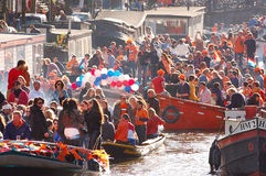 Celebration. Amsterdam - April 30: Celebration of queensday on a Amsterdam canal with houseboats on April 30, 2013 in Amsterdam, The Netherlands Royalty Free Stock Photo