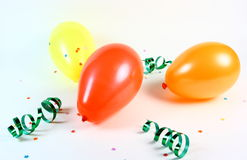 Celebration Balloons. Three colorful balloons with streamers and confetti photographed on a white background Royalty Free Stock Photography