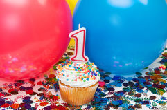 Celebration with Balloons, Confetti, and Cupcake. Celebration with balloons, confetti, cupcake, and number 1 candle Royalty Free Stock Image