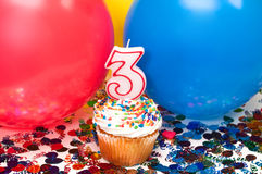 Celebration with Balloons, Confetti, and Cupcake. Celebration with balloons, confetti, cupcake, and number 3 candle Stock Image