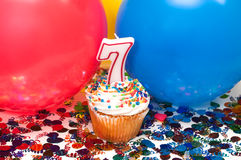 Celebration with Balloons, Confetti, and Cupcake. Celebration with balloons, confetti, cupcake, and number 7 candle Royalty Free Stock Images