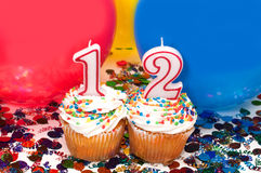 Celebration with Balloons, Confetti, and Cupcake. Celebration with balloons, confetti, cupcake, and number 12 candle Royalty Free Stock Photography
