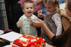 Celebration Birthday. Mum suggests the son to blow out candles. The 2-year-old little boy radiates joy. The sister ranks with a Birthday cake and she very much stock photography