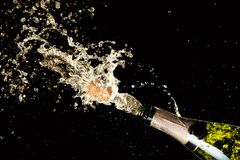 Celebration of birthday, anniversary or Christmas theme. Explosion of splashing champagne sparkling wine with flying cork out of t. He bottle on black background stock photography