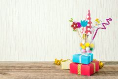 Celebration, Birthday party background with colorful party hat,. Confetti, gift boxes and other decor. Colorful accessories for parties on wooden table. Copy royalty free stock images