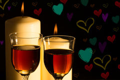 Celebration candlelight with wine. Wine glasses in candlelight with colored background hearts Stock Photos