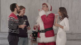 Celebration of Christmas. Friends are blowing. Friends celebrate Christmas and have fun blowing favor horns. Professional shot on BMCC RAW with high dynamic stock footage