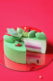Celebration (Christmas) Matcha and Currants Mousse Cake. On a bright red background. on a bright red background Royalty Free Stock Photos