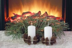 Celebration of Christmas. Wax candles decorated with fir cones of garlands on a white lace tablecloth against the background of a stock photography