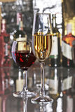 Celebration composition with two glasses white and red wine grapes on mirror table. Stock Photos