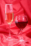 Celebration composition with two glasses white wine grapes on red backgroumd. Royalty Free Stock Images