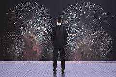Celebration concept. Back view of young businessman on wooden pier watching fireworks. Celebration concept Stock Photography