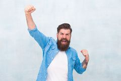 Celebration concept. Brutal handsome hipster man on grey wall background. Bearded man trendy hipster style. Cheerful royalty free stock images