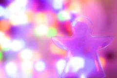 celebration concept - christmas figure of an angel and abstract blurred lights on background. Blue, purple, orange colors. royalty free stock image