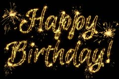 Celebration concept. Text Happy Birthday written sparkling sparklers isolated on black background. Overlay template for greeting