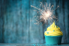 Celebration cupcake. Cupcake with yellow buttercream and a sparkler Stock Photography