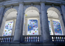 Celebration Day. Painting of building with stately columns and view beyond to blue sky, white clouds and many released colorful balloons with one trapped one Stock Photography