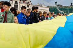 Celebration of the Day of the State Flag of Ukraine in Uzhgorod. Uzhgorod, Ukraine - August 23, 2017: Local schoolchildren and priests carry a 100-meter flag stock photo