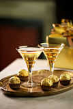 Celebration Drinks. Two vintage glasses with sparkling drink and chocolates and presents Royalty Free Stock Photo