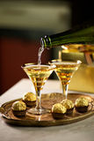 Celebration Drinks. Two vintage glasses with sparkling drink and chocolates and presents Royalty Free Stock Image