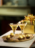 Celebration Drinks. Two vintage glasses with sparkling drink and chocolates and presents Stock Photo