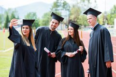 Celebration Education Graduation Student Success Learning Concept. Graduated students taking selfie. stock photo