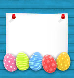 Celebration empty paper card with Easter ornamental eggs on wood Stock Image