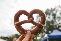 Celebration of the famous German beer festival Oktoberfest. The person holds in his hand a traditional pretzel called. Brezel in the background of a blurry Stock Photos