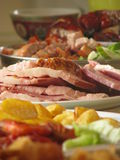 Celebration food spread. A variety of food in a party spread mixing Asian roast meats and western ham and sauteed potatoes Stock Images