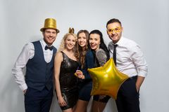 Happy friends with golden party props posing royalty free stock images