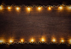 Celebration garland of light bulbs. On wooden background copy space for inscriptions stock photography