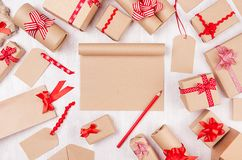 Celebration gifts background with blank paper and red pencil, different presents with funny red bows on soft white wood table. stock photos