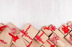 Celebration gifts background - different presents of craft paper wrapped with red ribbons and bows, blank labels on white wood. stock image
