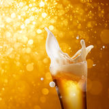 Celebration. Glass of splashing beer against golden bokeh background royalty free stock images