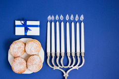 Celebration of Hanukkah. Candlestick with fried donuts, gift, on white and blue background.  Stock Image