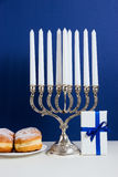 Celebration of Hanukkah. Candlestick with fried donuts, gift, on white and blue background Royalty Free Stock Photos