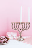 Celebration of Hanukkah, the first day. Candlestick, fried donuts and gift, on white and pink background.  Stock Images