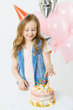 Celebration. Happy little curly girl in festive cap sit near birthday cake and smiling. Balloons on the background Stock Photo