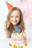 Celebration. Happy little curly girl in festive cap sit near birthday cake and smiling. Balloons on the background Royalty Free Stock Photo
