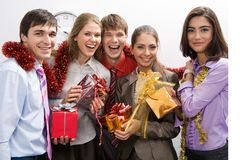 Celebration of holiday. Happy businessgroup with colorful presents in hands looking at camera and smiling Royalty Free Stock Photo