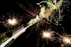 Celebration and holiday theme. Bright festive Christmas sparklers with fireworks and splashing champagne with popping cork on blac Stock Images