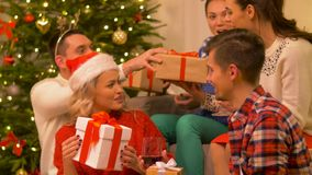 Friends celebrating christmas and giving presents. Celebration and holidays concept - happy friends with glasses celebrating christmas at home party, giving stock footage