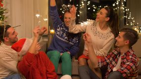 Happy friends celebrating christmas at home party. Celebration and holidays concept - happy friends with sparklers celebrating christmas at home party stock video footage