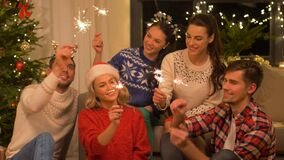 Happy friends celebrating christmas at home party. Celebration and holidays concept - happy friends with sparklers celebrating christmas at home party stock video