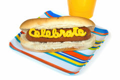 Celebration hot dog. Celebration in mustard on a hot dog with yellow cup and striped plate isolated on white stock photo