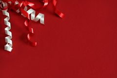 Celebration Label. Red card decorated with red and white ribbons with copyspace Stock Photos