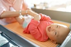Celebration of life: cute Asian baby smiling while having diaper change. Celebration of life: cute Asian baby having diaper change royalty free stock photography