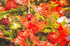 Celebration of New Year and Christmas background. Details of a Christmas tree. Detail shot of Christmas tree branches with Christm. As toys and red ribbons Royalty Free Stock Photo